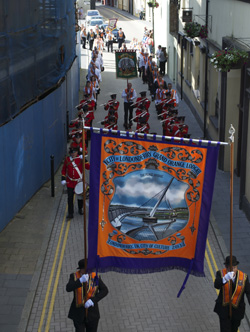 The Orange Order, a Unionist organization, marches in preparation for a large march on the 12th of July. The banner for the City of Londonderry lodge depicts the Peace Bridge, a pedestrian bridge built to connect the 'Waterside' and 'Cityside' areas of the city.
