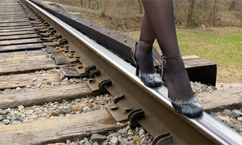 "Alison Stine posted this photo of herself walking on a train rail on her Facebook as a ""clue"" before her new novel was announced."