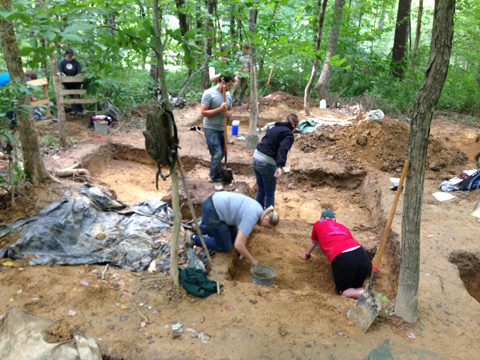 Sarah Hinkelman and Keeleigh Davis are in the foreground; Cameron Fortin is standing in the center with a shovel.