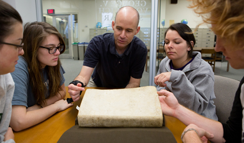 Clockwise, from left: Ohio University students Chloe Farmer, Michele Post, Brittany Centorbi, and Josh Davis, as well as Associate Professor Bob Klein, center, examine an ancient math text during a special presentation at Alden Library on April 18, 2014. During the presentation, students enrolled in Professor Klein's History of Mathematics course viewed some of the centuries-old math manuscripts that are stored in the library's Special Collections section. Photo by Lauren Pond