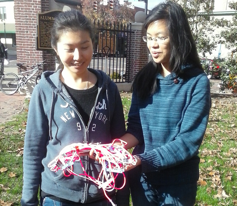 Graduate student assistants Lu Tian and Susan Zhang holding a clump of cords representing DNA in its bunched-up form.