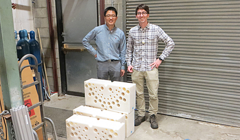 Nuclear Physicists Tony Ahn and Zach Meisel stand on the dock at the Edwards Accelerator Lab and behind section of the polyethylene blocks used to slow down neutrons. The holes are where the detectors are placed. Dr. Tony Ahn and Dr. Zach Meisel stand on the dock at the Edwards Accelerator Lab and behind section of the polyethylene blocks used to slow down neutrons. The holes are where the detectors are placed.
