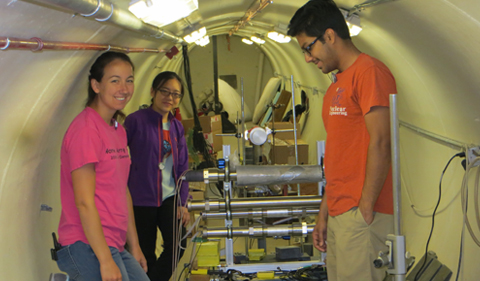 Setting up the helium detectors are from from left: Catlin Barker, Tin Zhu and Sasmit Gokhal. The round detector is a standard liquid scintillator with organometallic tin added to improve the separation between neutrons and gammas.
