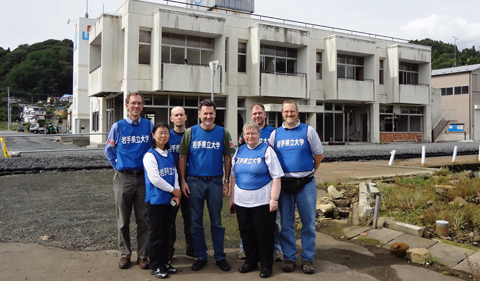 Dr. Christopher Thompson, with (L-R) Dr. Joe Shields, OHIO alums Yuko Kuwahara, and Todd Fouts, Dr. Tom Scanlan, Provost Pam Benoit, and OHIO alum and Chubu University professor Greg King in front of a destroyed fisheries building on the waterfront in Otsuchi, Iwate in September, 2012.