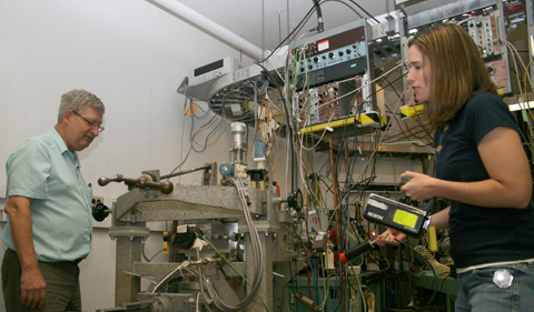 Parker and Massey use a Geiger-Mueller counter to check for activation in the chamber. Massey is in charge of radiation safety in the lab, and helps guide researchers what levels are acceptible for working in an area, as well as if special precautions are needed for moving or storing equipment.