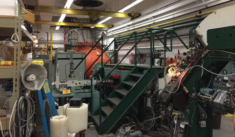 The protons are accelerated in a two-step process in the tandem, bent 90 degrees through the analyzing magnet to filter the energy, and travel toward the left to the small target room after another slight bend through the switching magnet.