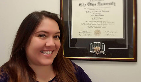 Dana Brown with her framed Ohio University degree on the wall next to her