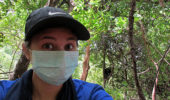 Nicole Wackerly in in Senegal with Fongoli chimp Bo (adult male) in the background. Because humans are so closely related to chimpanzees, we wear masks when in close proximity as a precaution against disease transmission.