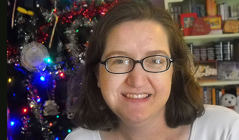 Jenny Shank, smiling, with decorated Christmas tree and bookshelves behind her