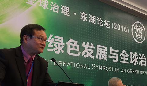 Jieli Li at podium with International Symposium sign behind him