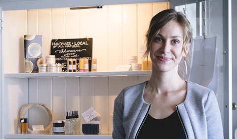 Kelsi Boyd next to display of naturally made body care products in a white cabinet