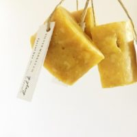 three yellow SM Co. handmade soaps hanging by string with a label