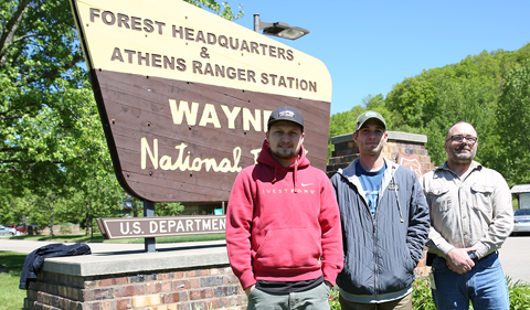 Interns Samuel Heckle and Zachary Matthews, with Wayne member, standing in front of Wayne National Forest sign