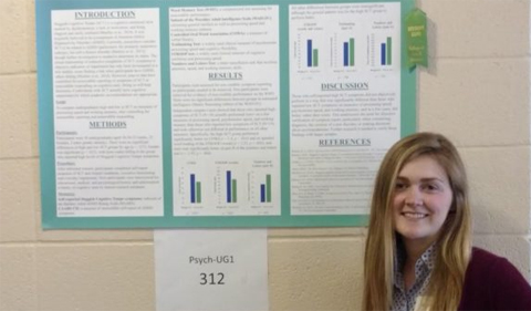 Jessica Smith presents her work on Sluggish Cognitive Tempo at a student research expo, shown her standing with her poster.