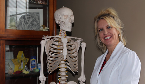Dr. Jodie Foster, in lab, with skeleton and white coat