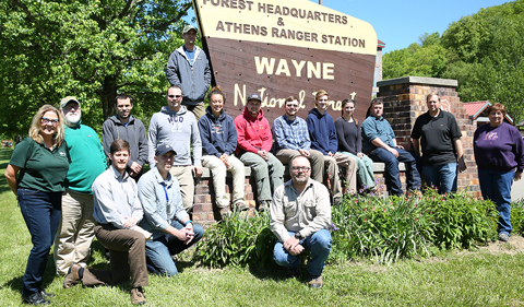 Ohio University interns with faculty and staff from OHIO and the Wayne National Forest, standing as a group in front of the Wayne sign.