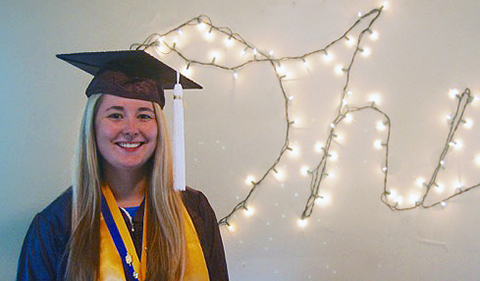 smiling Rachel Neal in cap and gown with honor cord and honor sash standing in front of light string that is shaped on the wall behind her to spell Ohio