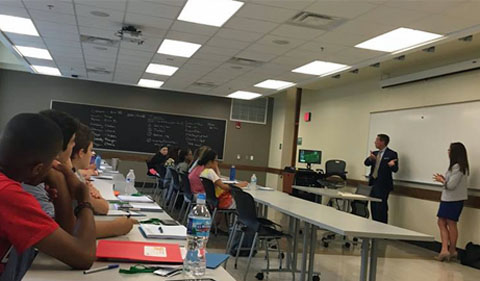 Attorneys James Linehan and Jessica Branner discuss criminal trials, with students watrching in the foreground.