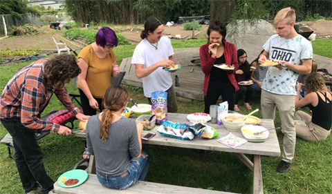 Students in Food Matters club eating at picnic table at Learning Gardens.