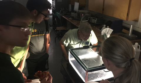 Dr. Thomas Massey demonstrates the tracks of cosmic rays as they pass through a cloud chamber.
