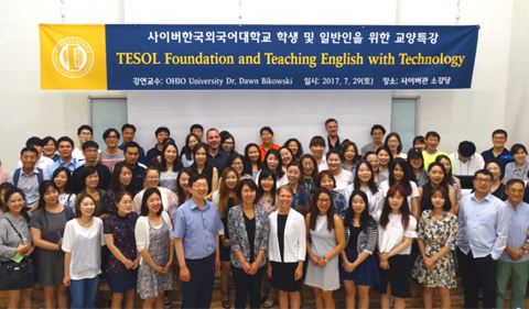 Students gather in South Korea for the TESOL Foundation and Teaching English with Technology conference with Ohio University. Group photo under banner.