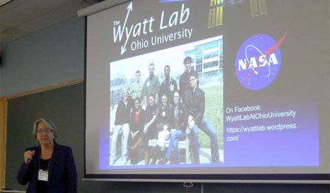 Dr. Sarah Wyatt talks about her experiment on the International Space Station, with slide showing NASA logo and group photo of her students.