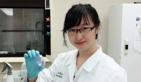 Xuan Wang, holding up sample in her white lab coat