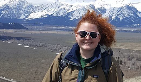 A smiling Adrianne Talmadge, wearing sunglasses and with wind-blowing hair and Tetons in the background
