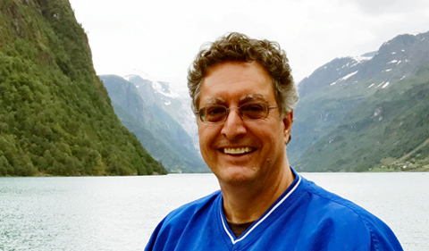 Dr. James Lein, with mountains, lake in background