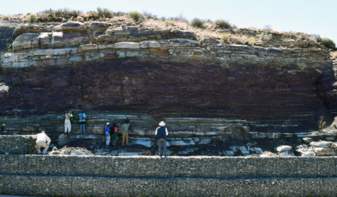 Ichnologists investigate a large Triassic burrow. Photo taken from a distance, with scientists working on a ledge.