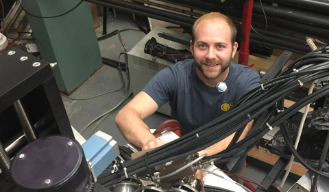ND Doctoral Student Bryant Vande Kolk adds a pulser cable to a detector to test its time of flight signal.