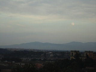 The moon rising over Rome's neighboring mountains.