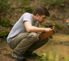 Daniel Williams, a student participating in the Ohio University Archaeological Field School, looks for bone fragments.  Photographer: Ben Wirtz Siegel