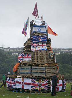 A bonfire built by some members of the republican community. Bonfires are very common in the summer, but most are built by loyalists to commemorate events like the Battle of the Boyne. They are politically charged events, as evidenced by the number of British flags and other symbols of unionism to be burned (loyalists burn nationalist symbols, such as the Irish tricolor).