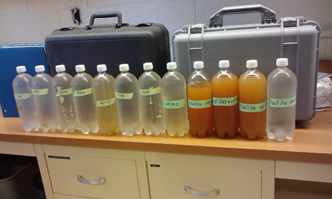 From right: Water collected from the headwaters above the doser (far right). The orange water is from the sacrifice zone, followed by clear water 11 to 12 miles downstream.