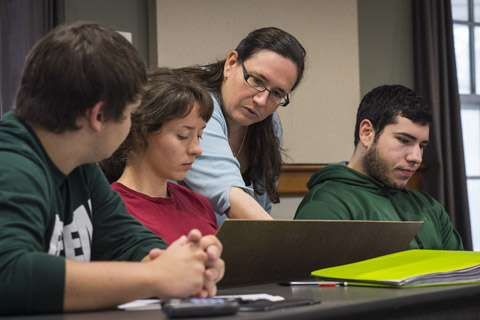 Dr. Julie Roche works with undergrads in small groups.