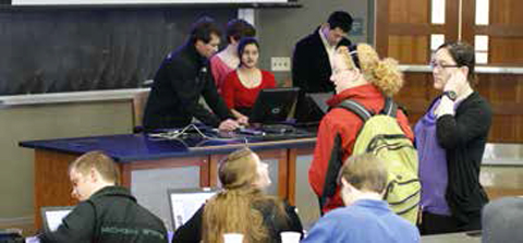 Students load their presentations on the computer prior to the start of the conference.
