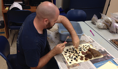 Nicholas Stillman cleans artifacts in the lab.