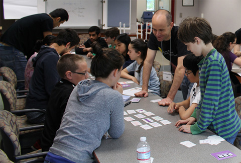 Bob Klein works with Math League participants (from left) Brandon, Maya, Jonathan and Garey on Geometry of the SET game.