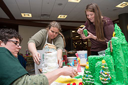 "College of Arts and Sciences employees (from left) Linda Schoeppner, Janice Bailey-Magill and Stevi Miller construct a ""75 Christmases in Oz"" themed gingerbread house.  Photographer: Ben Siegel/Ohio University"