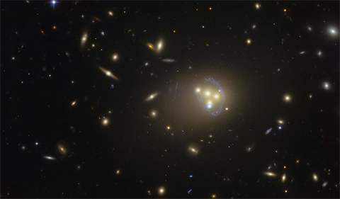 This image from the NASA/ESA Hubble Space Telescope shows the rich galaxy cluster Abell 3827. The strange blue structures surrounding the central galaxies are gravitationally lensed views of a much more distant galaxy behind the cluster. Observations of the central four merging galaxies have provided hints that the dark matter around one of the galaxies is not moving with the galaxy itself, possibly implying dark matter-dark matter interactions of an unknown nature are occurring. Credit: ESO