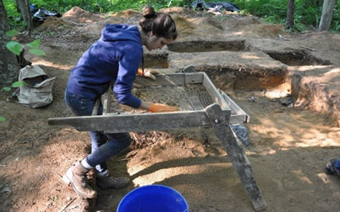A student sifts dirt from the dig.