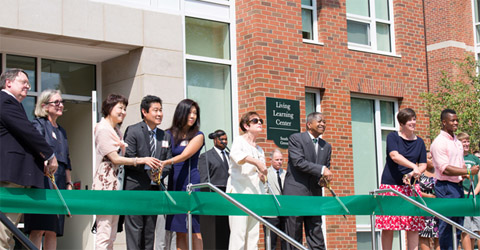 (From left) Stephen Sowle, Leslie Sowle, Norico Tanaka-Wada, Tim Tanaka, Tamao Tanaka, Janey Smith, President Roderick J. McDavis, Interim Vice President for Student Affairs and Dean of Students Jenny Hall-Jones, and Jovon Johnson cut the ribbon marking the official grand opening of Ohio University's four new residence halls and Living Learning Center. Photo by Jasmine Beaubien