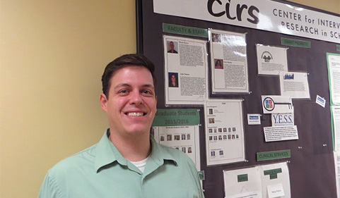 Psychology graduate student Alex Holdaway poses in front of a CIRS bulletin board