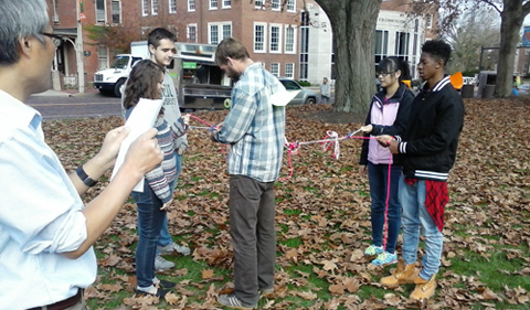 "Students begin to unwind the ""DNA strands"" as Dr. Hua describes the process of DNA replication."