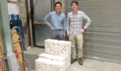 Nuclear physicists Tony Ahn and Zach Meisel stand on the dock at the Edwards Accelerator Lab and behind section of the polyethylene blocks used to slow down neutrons. The holes are where the detectors are placed.
