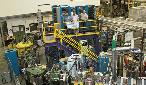 L to R: Giri and Paneru are joined by Dr. Chris Ruiz, Research Scientist at TRIUMF. The group stands above the DRAGON apparatus, a recoil separator which detects the oxygen produced when the carbon beam strikes the helium target.