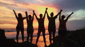 Five people stand with arms raised in from of ocean