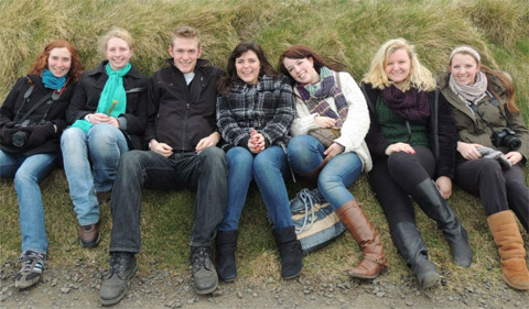 Students on Spring Break in Ireland, sitting side by side on a grassy hill