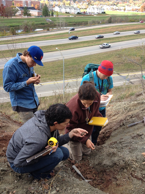 Chris Jorgensen, Michael Blair, Lauren Johnson, and Alex Conti examine evidence of burrowing animals in ancient soil deposits on Witches's Hill in Athens.